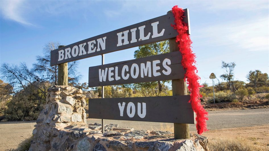A feather boa adorns the welcome sign to Broken Hill. Credit: Destination NSW.