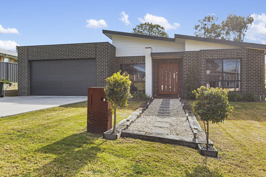 grey brick house with brown front door and grey path and double garage