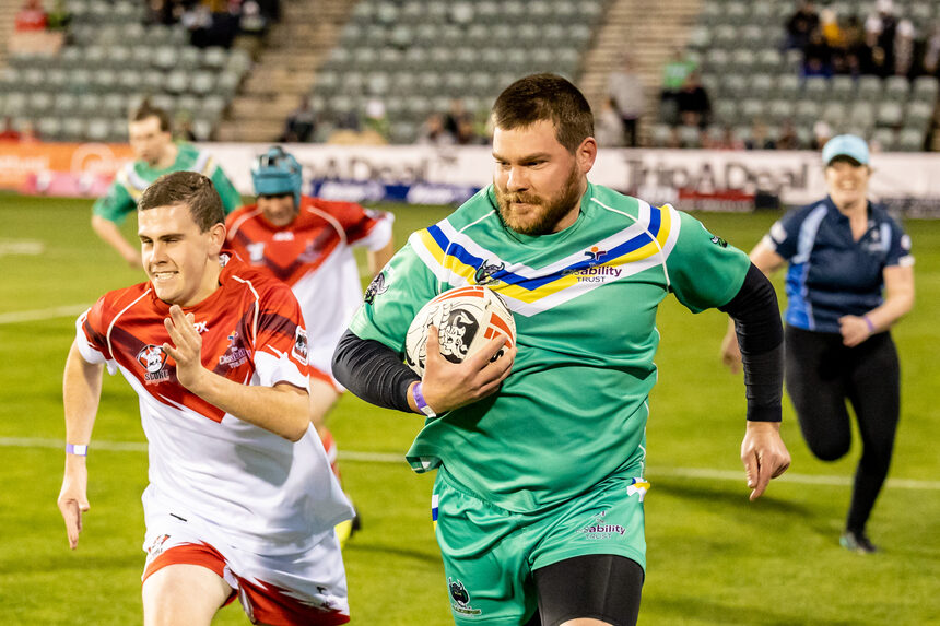 two people playing rugby one in green shirt and one in white shirt, one in green shirt running with ball