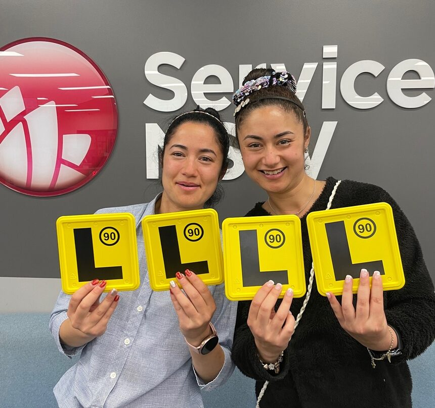 Twin girls standing outside Service NSW Office holding up L plates