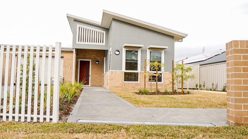 Cream and grey home with white fence