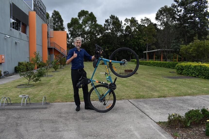 Man holding a bike at an angle