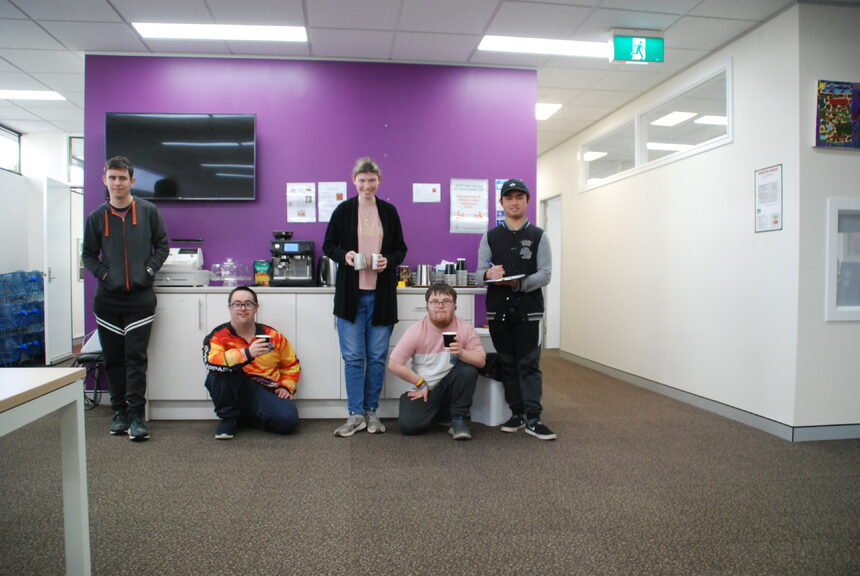 Group of people standing in front of coffee machine and purple wall