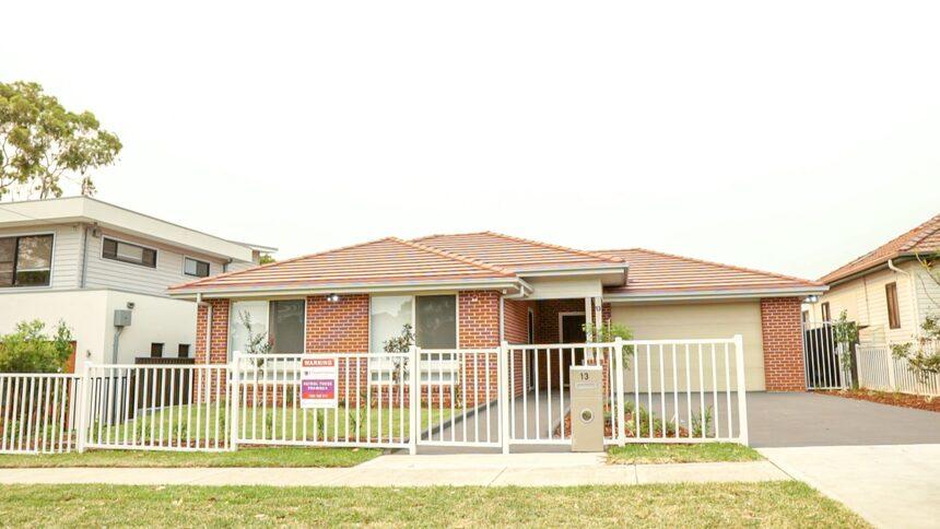 Orange brick home with large windows, garage and white fence