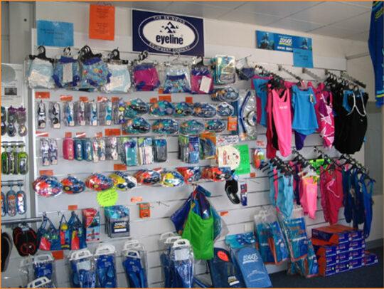 Image of wide range of aquatic gear hanging for sale on wall-mounted racks: goggles, flippers, swimsuits, nappies, snorkels, etc