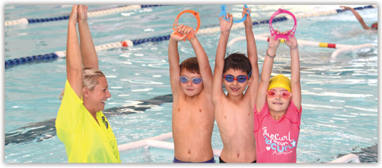 Swim instructor and three school age children in pool holding up coloured rings