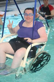 Woman in wheelchair suspended in pool giving peace sign with right hand