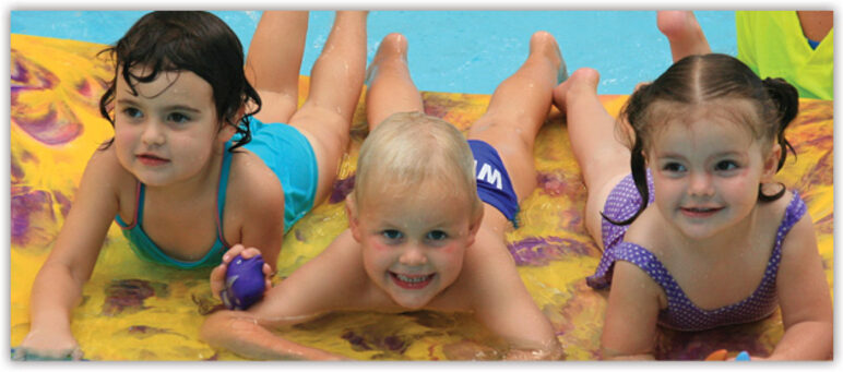 Three pre-school age children lying on flotation device