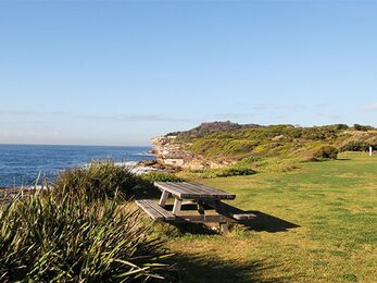 View of flat grassy area with picnic table and rugged coastline in the distance Photo Natasha