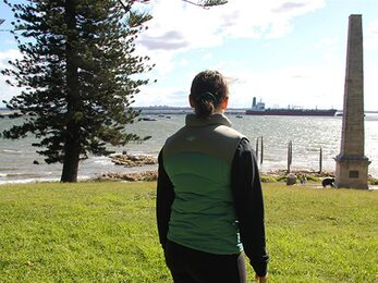 Girl looking out past Captain Cook Monument in Kurnell Kamay Botany Bay National Park Photo