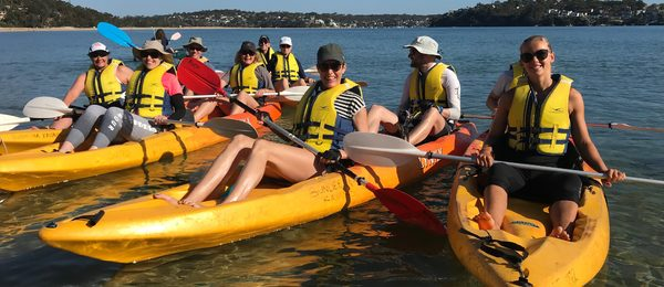 People in double kayaks rafted together along Bundeena beaches